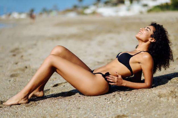 young-arabic-woman-with-beautiful-body-in-swimwear-lying-on-the-beach-sand_1139-1580